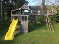 Children's climbing frame with slide, swings, ladders, monkey bars, climbing wall and playhouse