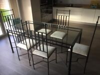 Glass dining table with metal frame and 6 chairs. Chairs match table. Will possibly split.