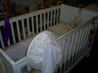 A white baby's cot in good condition, no mattress