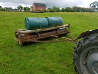 Tractor land field paddock roller has water drums on top for extra weight