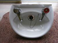 Small round ceramic Sink with taps.