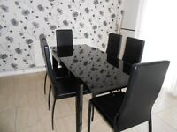 NEARLY NEW GLASS AND BLACK EXTENDABLE DINING SUITE