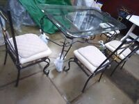 Glass table and chairs...wrought iron ..heavy item.