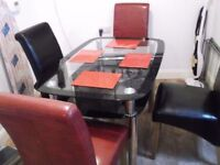 TWIN TIER GLASS DINING TABLE WITH 4 LEATHER CHAIRS 1 YEAR OLD