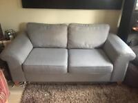 Grey fabric sofa with matching foot stool