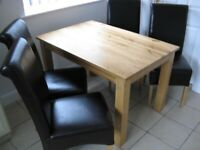 Oak table and four matching bicast leather chairs.