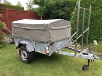 Large trailer with high and low frame, cover and spare wheel.