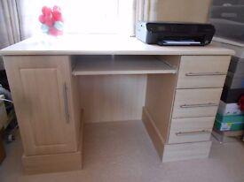 Light beech three drawer and one cupboard desk. has shelf if for use as a computer desk