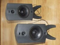 Two dark-grey speakers with a black amplifier.