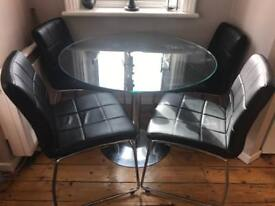 Round glass top dining table + 4 black leather chrome chairs