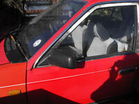 red mazda 323 4 door saloon