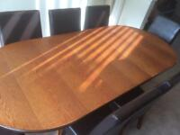 Heavy sold oak dining table with 7 chairs and a large drink and display cabinet