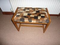 Wooden stool with padded upholstered seat.