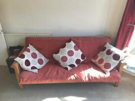 Large red futon with solid wood base - free to collect