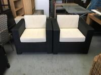 Two black and white rattan chairs