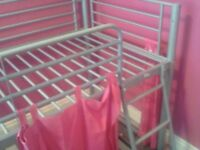 Child's cabin bed with pink curtains