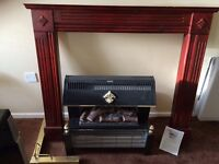 Electric fire, log effect. Wooden mantel surround. Metal extending hearth fender.