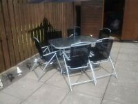 Glass table with 6 folding chairs and parasol with weight