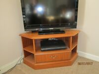 TV stand to fit in corner of room. Oak finish. One large drawer with several shelves.