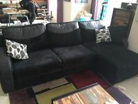Black corduroy corner sofa bed with chaise longue