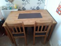 Lovely wooden dining table with two chairs and a bench