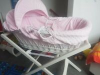 Pink moses basket with white wooden stand