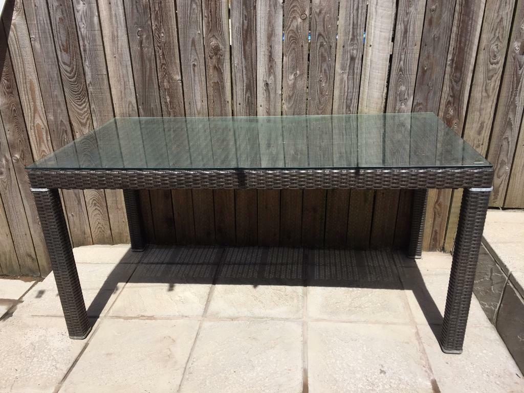 """Rattan garden table no chairsin Ebbw Vale, Blaenau Gwent - In very good condition Measures 63 x 31.5 """" Has tempered glass top Brown rattan, no chairs Collection from Cwm, NP23"""