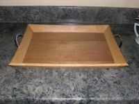 A wooden tray with silver coloured handles.
