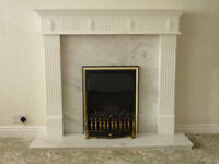 White wooden fire surround with marble hearth and back plate with brass electric fire..