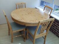 Pine Dining Table round extending to oval with 4 upholstered chairs.
