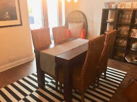 Dining Table and 4 Chairs , all in good condition. Dark wood with raffia type seats.