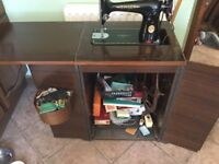 Singer sewing machine in cabinet for sale in good working order and with many extras.