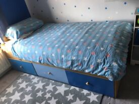 Children's bed frame with blue storage drawers