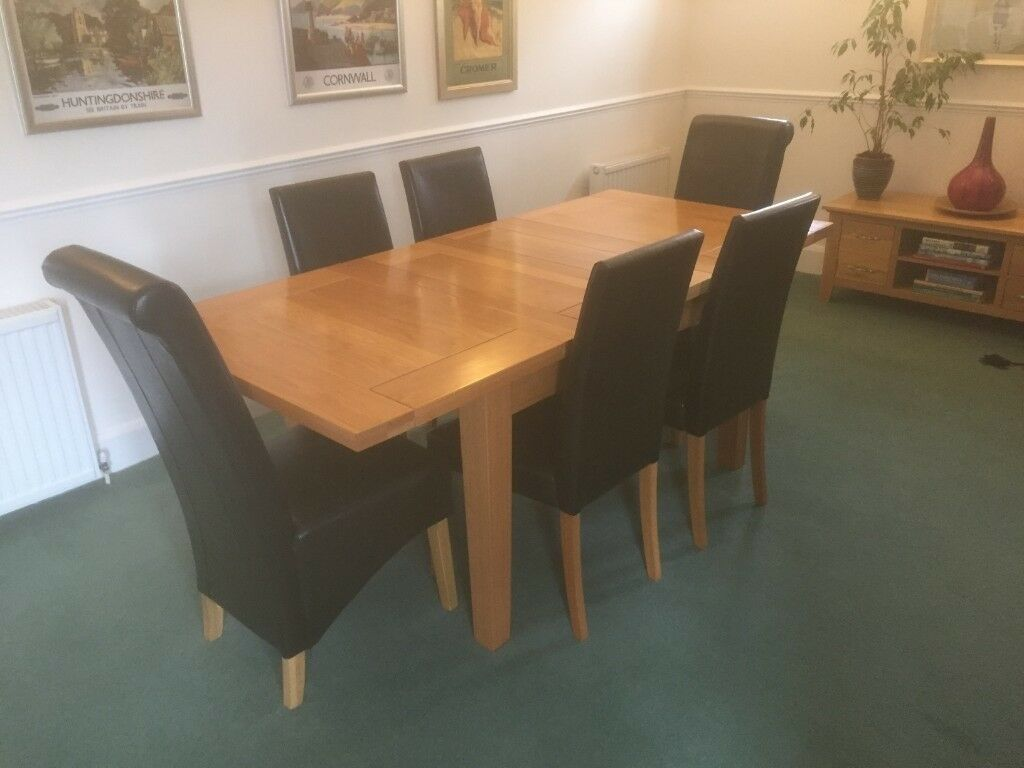 Lovely extending solid oak dining table 6 black leather chairs
