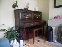 100 year old upright piano with candle stick holders.