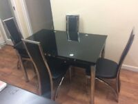 Black glass dining table with extending sides with 4 chairs