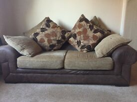 Brown two seater sofa with patterned cushions