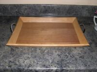 A wooden serving tray with metal handles.