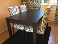 Black wooden extending dinning table with 4 chairs + 6 removable washable chair covers.