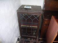 small dark wood cabinet with glass door