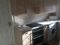 Maple coloured fitted kitchen.