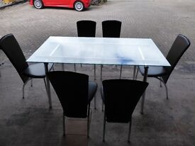 Glass and chrome dining table with 6 chairs. ( two sets) Good condition