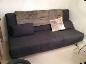 IKEA BEDDINGE LOVAS Three-seat sofa bed. Dark grey with two rectangular cushions.