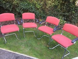 A set of four stacking chromed-steel framed upholstered arm chairs