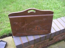 A 1960's wooden magazine rack with oriental carvings.