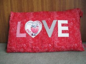 Beautiful red cushion with word 'LOVE' appliqued on