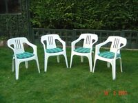 Four White Plastic Patio Chairs with Seat Cushions. Can Deliver