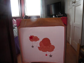 Baby girls pink travel cot with matching quilt.