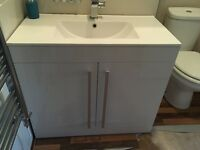 White gloss vanity unit with basin, taps and pop up waste.