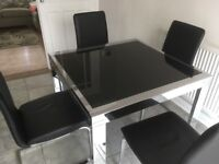 Glass topped extending table and chairs
